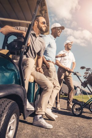 group of multiethnic friends standing near golf cart and looking away