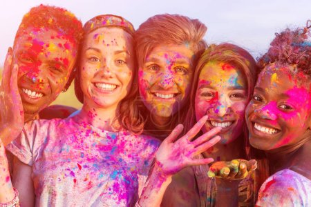 happy young multiethnic friends having fun with colorful powder at holi festival and looking at camera