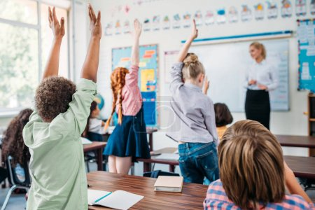 group of kids raising hands in class to answer teachers question