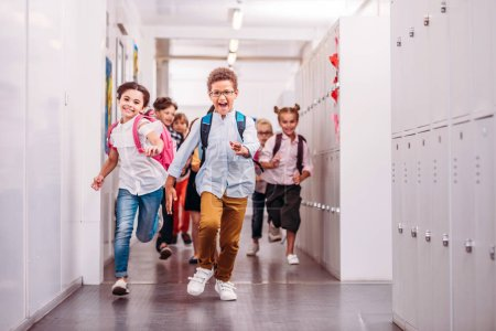 group of adorable pupils running through school corridor at camera