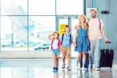 front view of smiling family walking on boarding together in airport, going on vacation