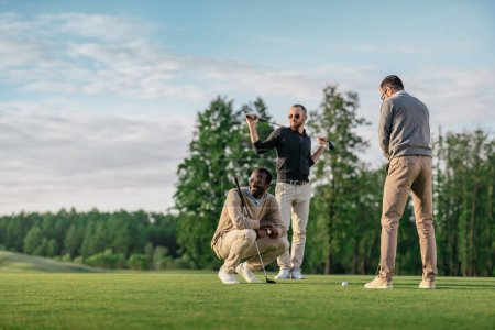 group of young stylish multicultural friends spending time together while playing golf
