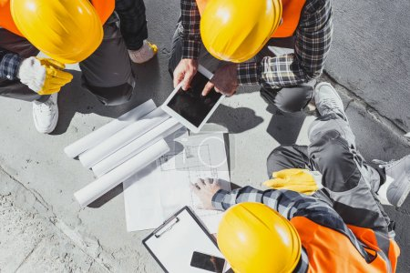 Photo for Top view of three construction workers sitting on concrete and discussing building plans - Royalty Free Image