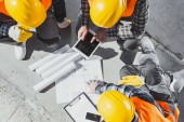 top view of three construction workers sitting on concrete and discussing building plans