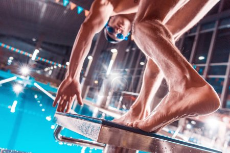 bottom view of athletic male swimmer jumping into competition swimming pool