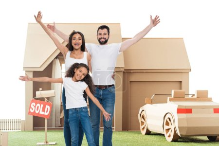 happy multi ethnic family with raised hands in front of new home