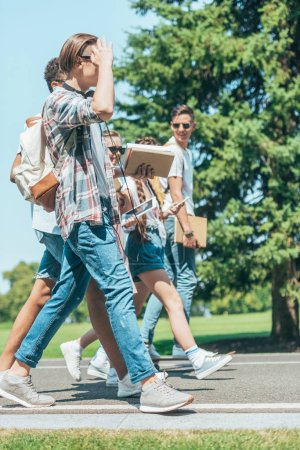 side view of teenage students with books and gadgets walking together in park
