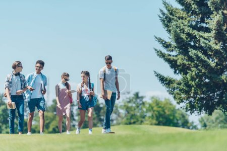 multiethnic teenage students with books and skateboard talking while walking together in park