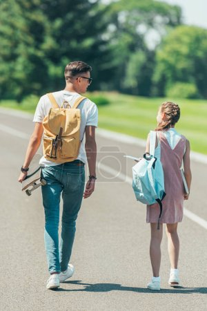 back view of teenage girl and boy with backpacks, books and skateboard walking and talking together in park