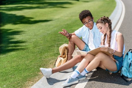 high angle view of multiethnic teenage boy and girl studying together in park