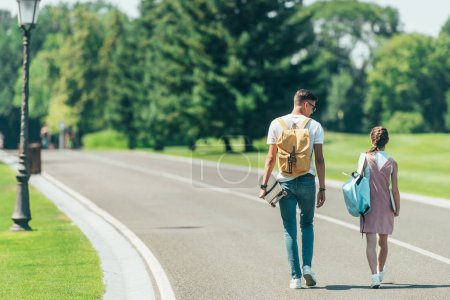 back view of teenage boy and girl with backpacks and skateboard walking together in park