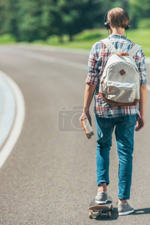back view of teenage boy in headphones holding books and riding skateboard in park
