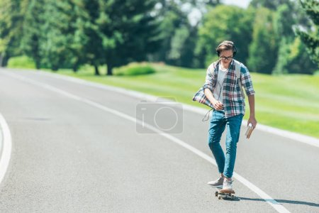 teenage boy in headphones holding books and riding skateboard in park