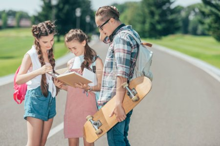 teenage students with backpacks and skateboard standing and reading book together in park