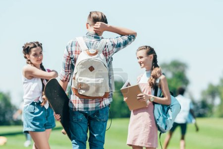 teenagers with books and skateboard standing and talking in park