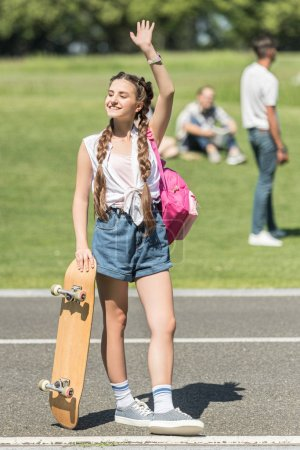 smiling teenage girl with skateboard and backpack waving hand and looking away in park