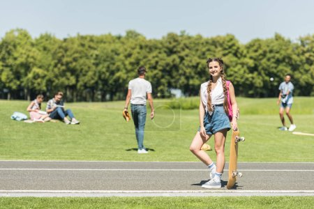 teenage girl with skateboard smiling at camera while friends spending time behind in park