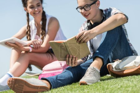 cropped shot of smiling teenage boy and girl studying with book and digital tablet in park