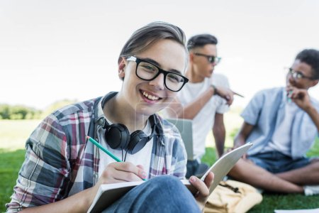 happy teenage boy taking notes and smiling at camera while studying with friends in park