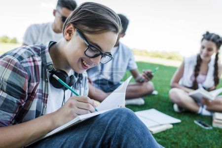 smiling teenage boy writing in notebook while studying with friends in park