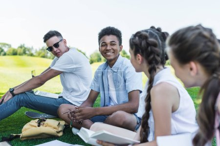 multiethnic group of teenage students smiling each other while studying together in park