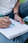 cropped shot of teenage student writing with pencil in blank notebook