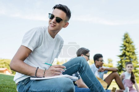smiling teenage boy in sunglasses taking notes and looking away while studying with friends in park