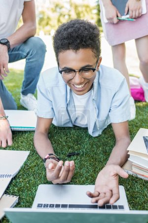 smiling african american boy using laptop while studying with friends in park