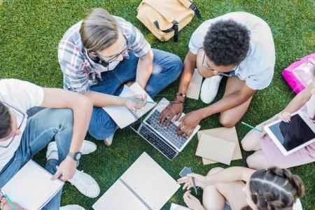 Foto de Vista aérea de estudiantes adolescentes multiétnicos con libros y dispositivos digitales en el Parque - Imagen libre de derechos