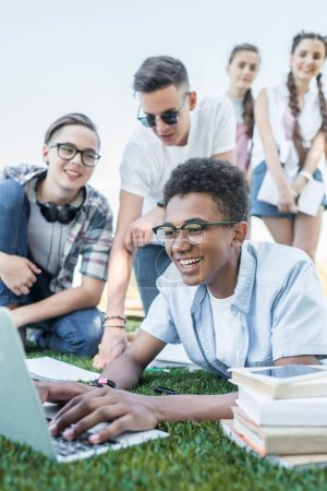 happy multiethnic teenage friends using laptop and studying in park