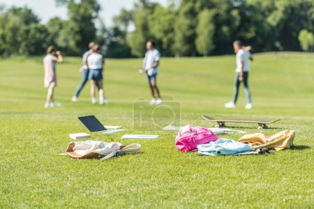 laptop, books, backpacks and skateboard on grass and teenagers playing behind in park