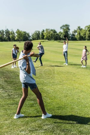 african american boy playing baseball with teenage friends in park