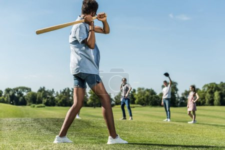 african american teenager holding baseball bat and playing with friends in park