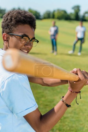 selective focus of smiling african american teenager playing baseball with friends in park