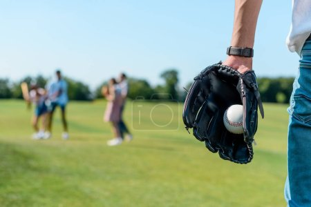 Photo for Cropped shot of teenager in baseball glove holding ball while playing with friends in park - Royalty Free Image