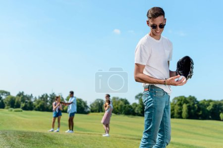 smiling teenage boy playing baseball with friends in park