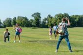 happy teenage friends playing baseball on green meadow in park