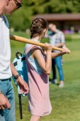 teenage girl holding baseball bat and playing with friends in park