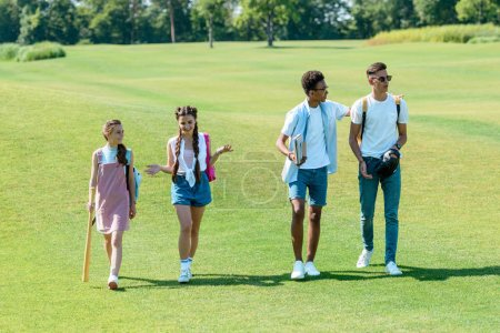 Photo for Multiethnic teenage students with books, backpacks and sport equipment walking together in park - Royalty Free Image