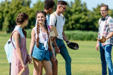 Foto de Amigos adolescentes felices con libros y mochilas jugando al béisbol en el Parque - Imagen libre de derechos