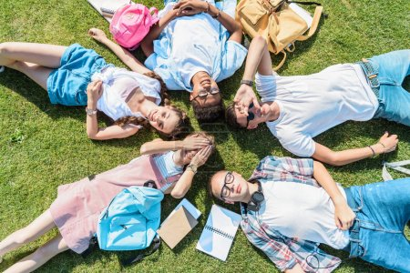 Photo for Top view of multiethnic teenage classmates with books and backpacks lying together on green meadow - Royalty Free Image