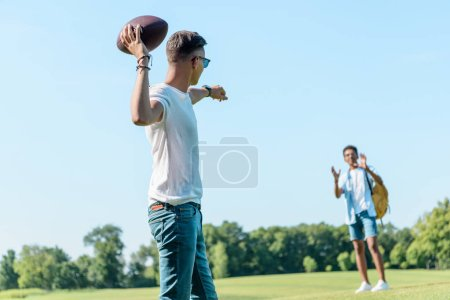 multiethnic teenage boys playing with rugby ball in park