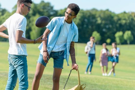 Photo for Teenage multiethnic friends playing with rugby ball while classmates walking behind in park - Royalty Free Image