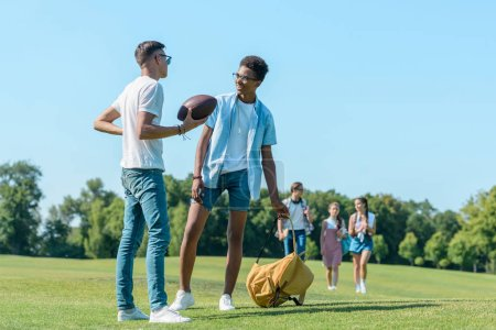 multiethnic boys playing with rugby ball while classmates walking behind in park