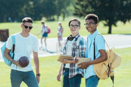 Foto de Adolescentes multiétnicos con libros y mochilas sonriendo a cámara en el Parque - Imagen libre de derechos
