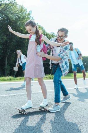 happy teenage boy teaching girl riding skateboard in park