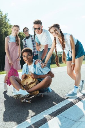 cheerful teenage multiethnic classmates with books and backpacks smiling at camera while having fun with skateboard in park