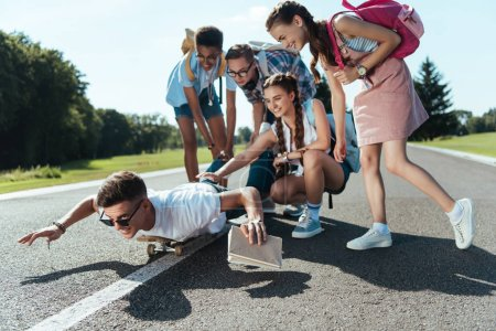 happy teenage classmates looking at smiling boy lying on skateboard in park