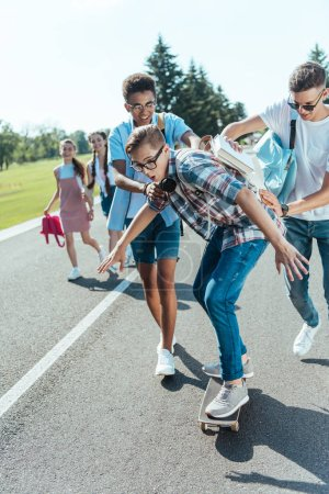Photo for Happy multiethnic teenage classmates having fun with skateboard and walking together in park - Royalty Free Image