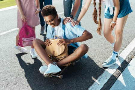 cropped shot of teenagers standing near smiling african american boy holding backpack and sitting on skateboard
